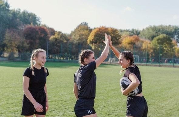 Meninas jogando futebol e comemorando um gol