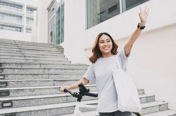 Menina dando tchau para alguém enquanto vai embora em uma bicicleta