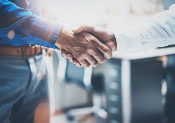 Imagem de dois homens apertando as mãos, como se estivessem acaba de fechar negócio