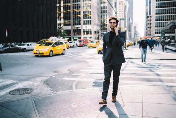 Imagem de um rapaz andando na rua de um país no exterior enquanto fala no celular