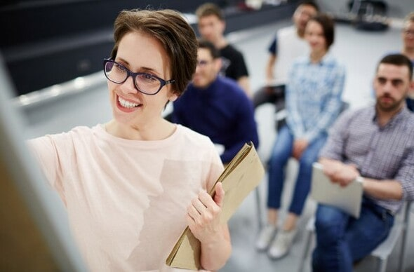 Professora de sucesso escrevendo na lousa com os alunos atrás dela