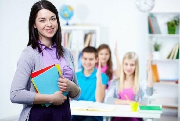 Professora de sucesso em frente aos alunos com as mãos levantadas