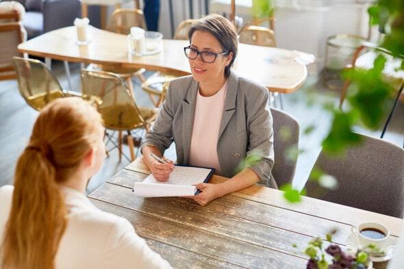 Imagem de uma entrevista de emprego. Tanto a entrevistadora quanto a entrevistada são mulheres.